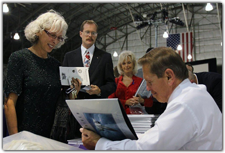 SR-71 pilot Brian Shul autographs copies of his book,