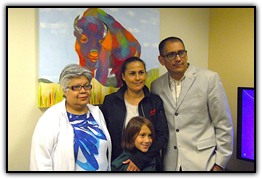 Arturo Garcia (far right) and his family with one of the paintings he donated to the Cancer Center during a reception May 26. Left to right: Garcia's mother, Maria Torres; wife Erika Tejeda; son Arturito