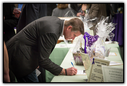 Featured speaker Sean Swarner bids on an auction item
